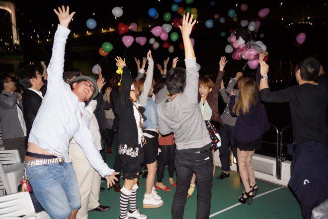 パーティ会場で風船を飛ばす若者