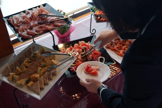 ビュッフェ形式で並ぶ料理をお皿に取る人