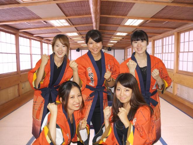 屋形船の中での法被を着た女性社員の集合写真