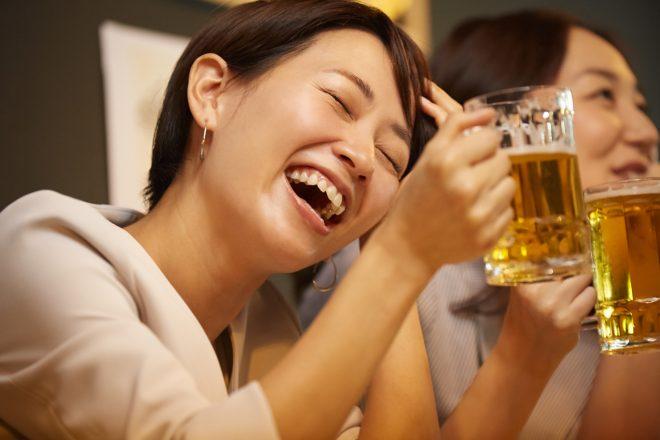 ビールを片手に楽しそうに笑っている女性