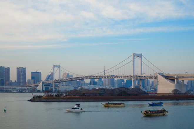大きな橋を背景に屋形船やクルーザーが海を進む