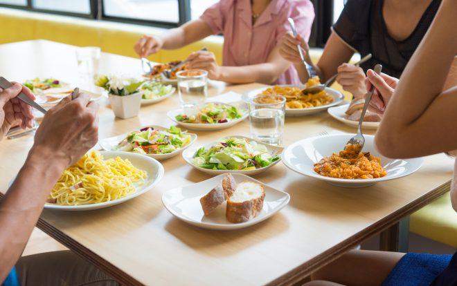 パスタやサラダを囲んでランチを楽しむ様子