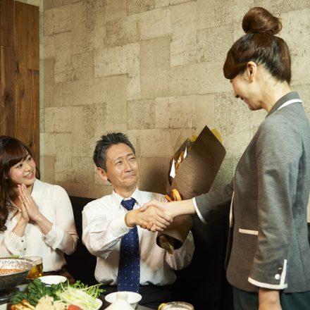 花束を持つ男性と握手する女性