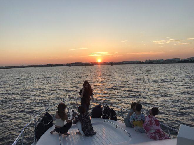 船のデッキへ出て夕日を見る女性グループ