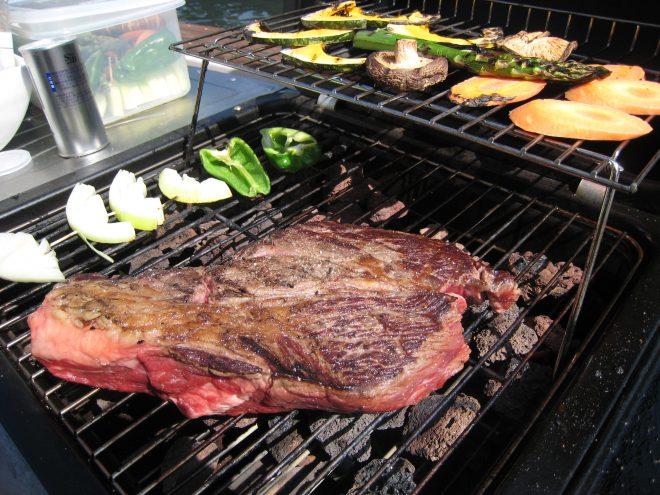 さまざまな種類の野菜と大きなお肉が網の上に乗っている