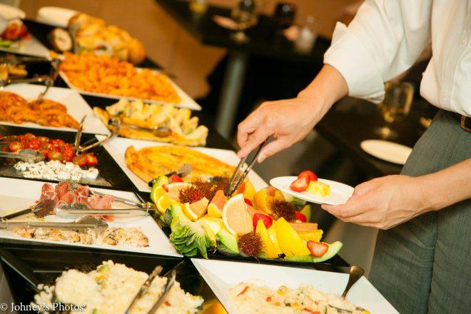 ずらりと並んだ料理からお皿に取り分ける人