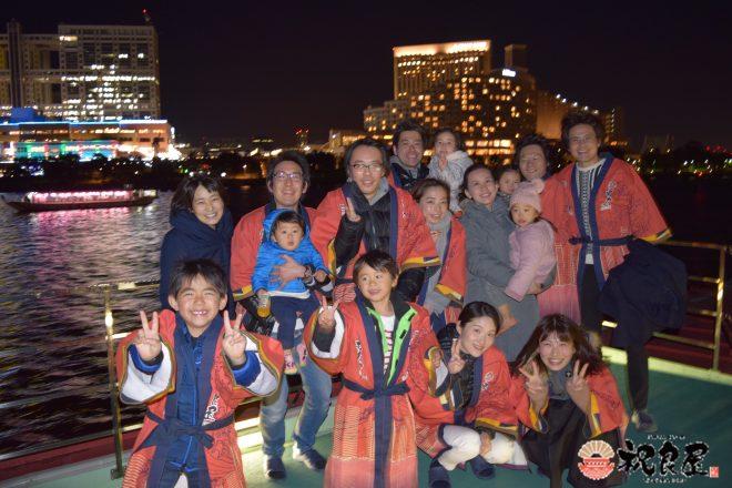 お台場の夜景を背景に、祝良屋法被を着た家族集合写真