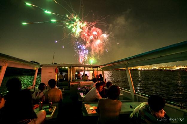 屋根のない船の上から花火観賞をする人たち