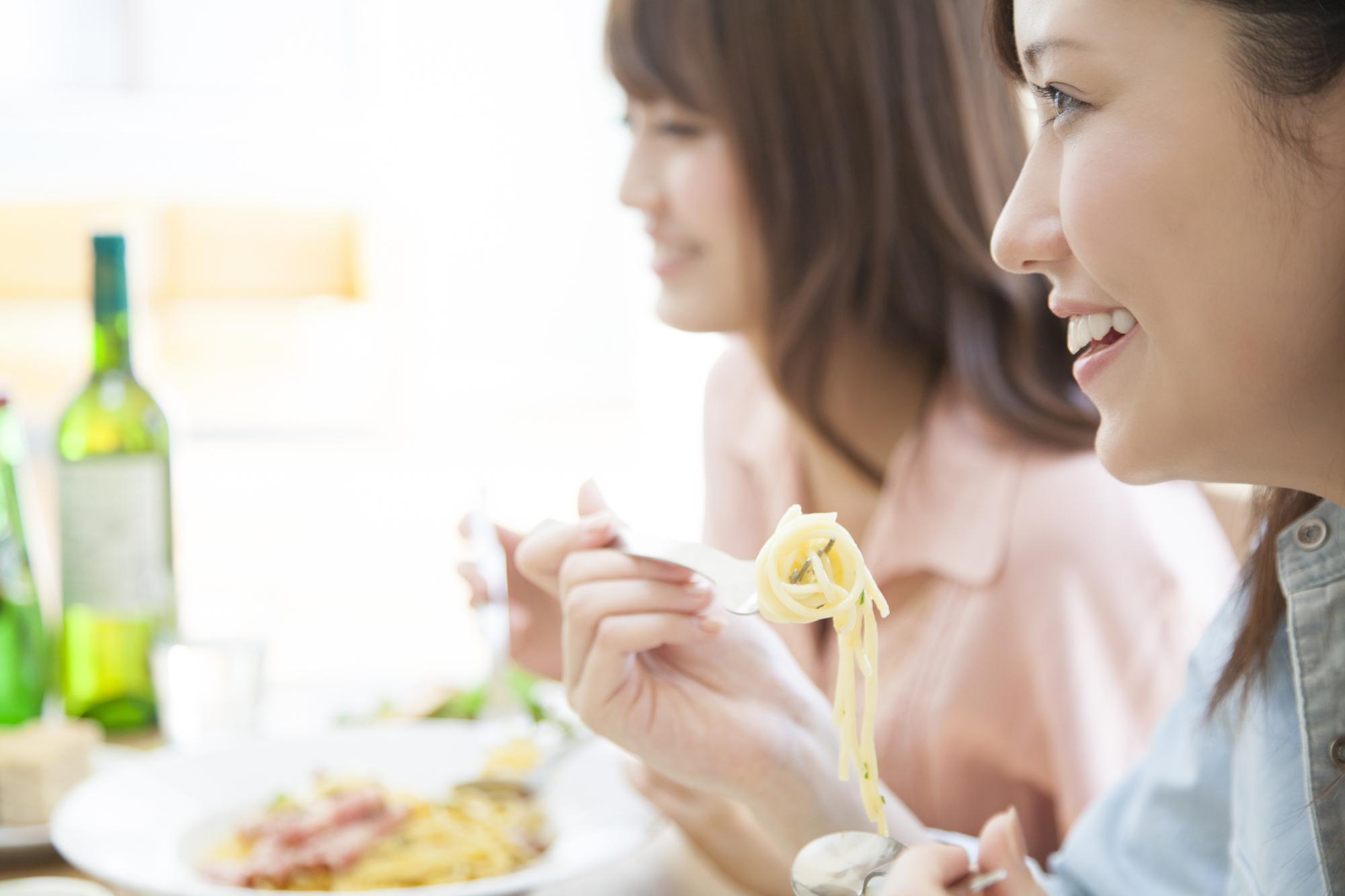 女性二人がパスタを食べている