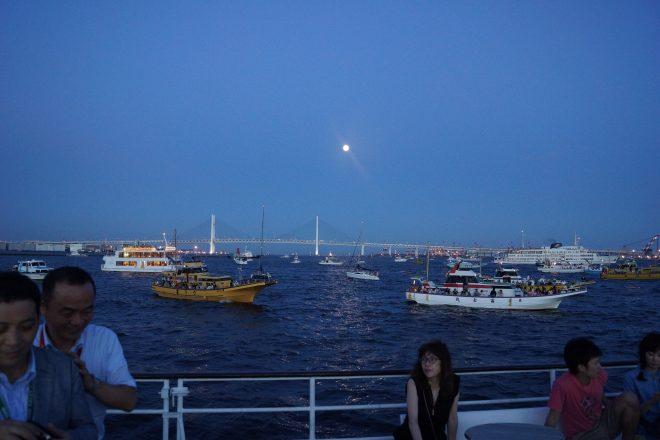 月の輝く海上にたくさんの船が停泊している様子