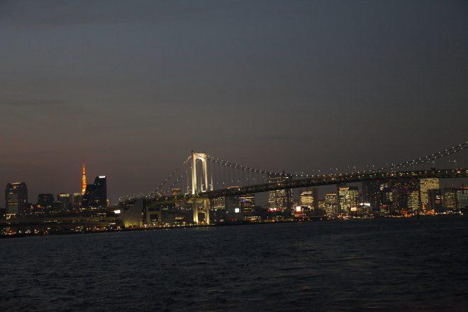 東京湾から見えるライトアップされたレインボーブリッジや東京タワー