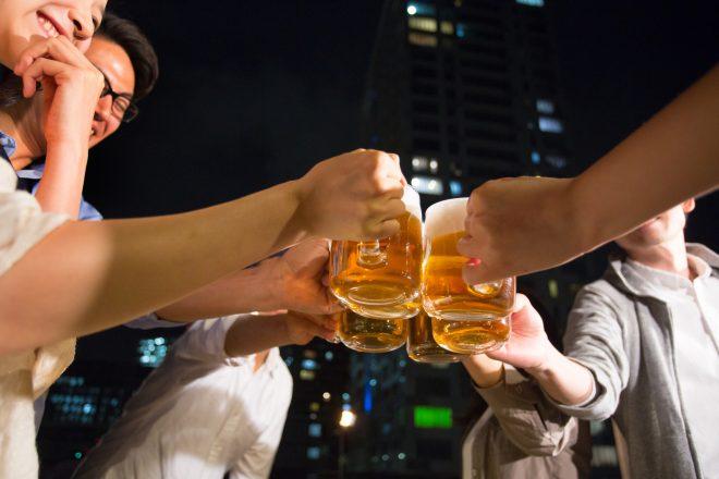 ビールを持って乾杯する男女グループ