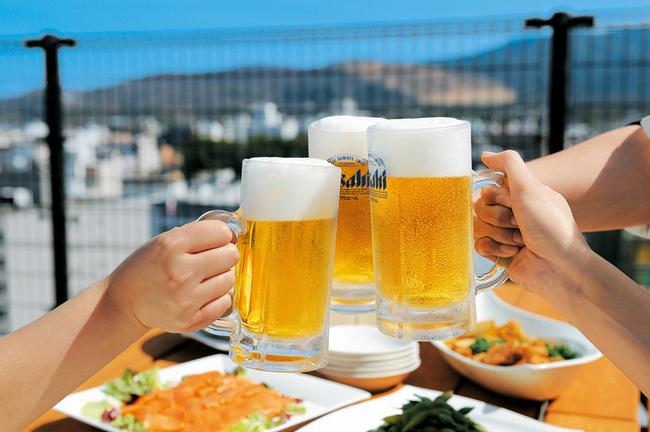ビアガーデンのテラス席で3人がビール乾杯