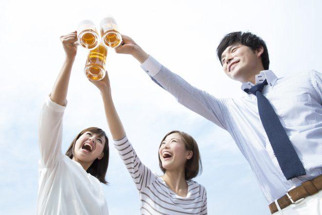 男女3人が青空に向かってビールで乾杯している様子
