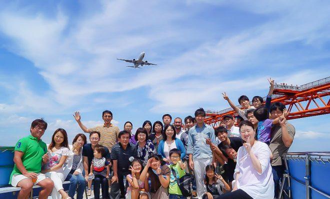 羽田沖で飛行機を背景に集合写真