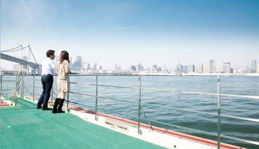 屋形船のデッキから東京湾の景色を眺める男女