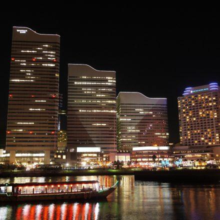高層ビルの明かりと提灯のついた屋形船