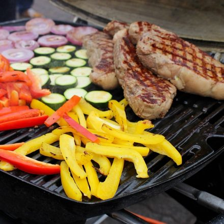 Steak grilled on the BBQ grill and colorful vegetables.