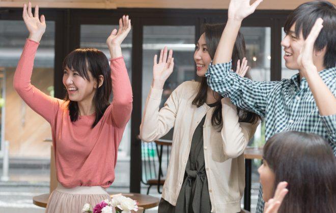 両手を上げて笑顔の男女