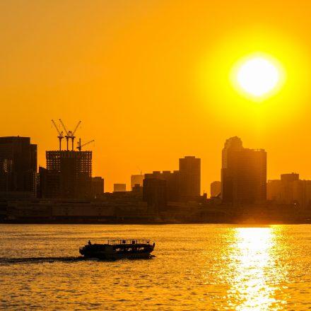 大きな夕日を背景に海を進む船