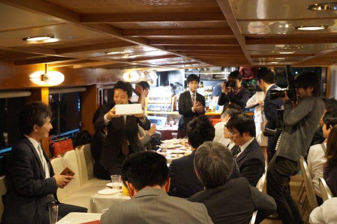 船内で盛り上がるスーツ姿の男性たち