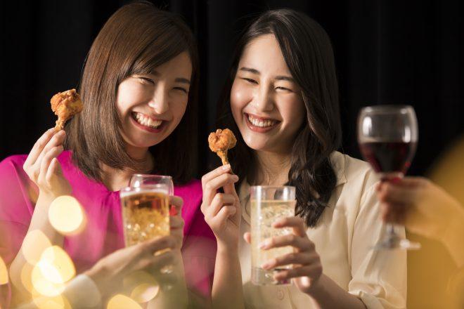 チキンとグラスを持った笑顔の女性