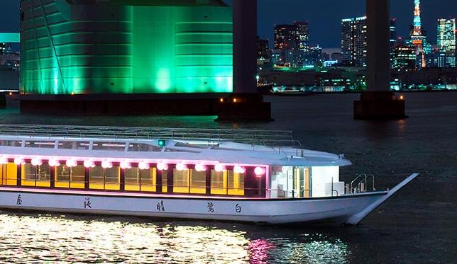 明かりの灯る屋形船と都会の夜景
