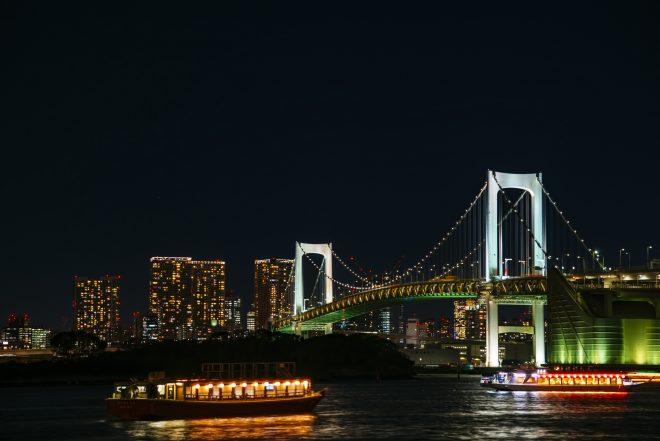 ライトアップされた屋形船と都会のイルミネーション