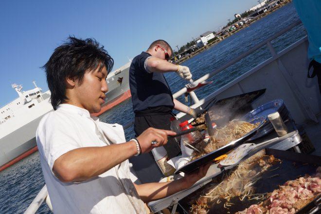 船の上でお肉などを焼く人