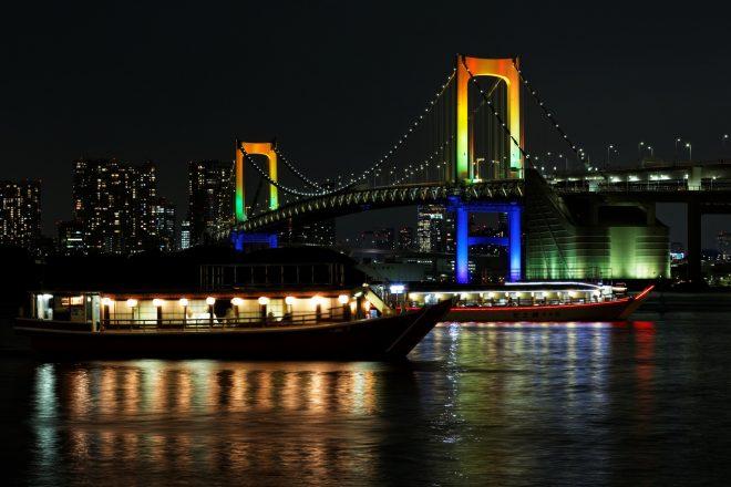 虹色にライトアップされたレインボーブリッジと屋形船