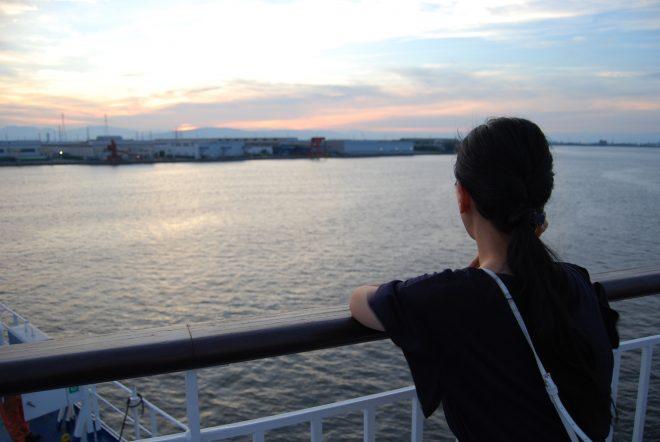 デッキから海を見つめる女性