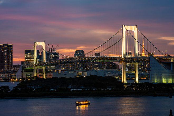 ライトアップされたレインボーブリッジと東京湾に浮かぶ屋形船