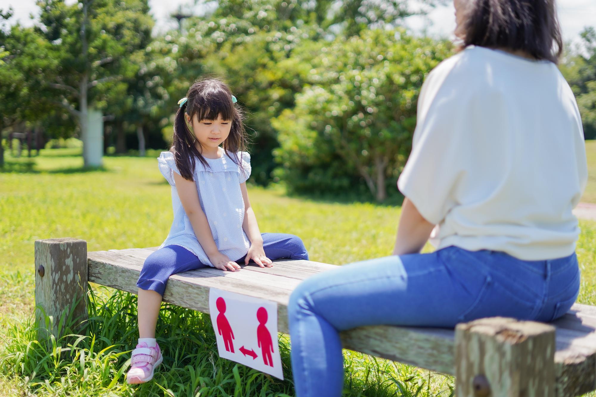 女の子とお母さんが距離を取りながらベンチに座る